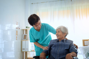 Delighted positive caregiver helping her patient, Nurse hugging his senior woman patient sitting on a wheelchair at home care