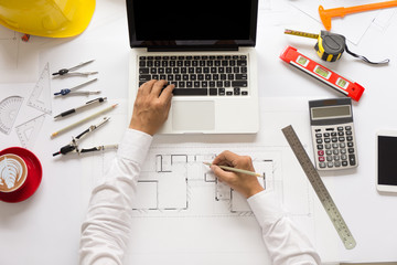 Top view, Architect hands working on blueprint plans with a pencil, a ruler, dividers, laptop, tablet and engineering tools.