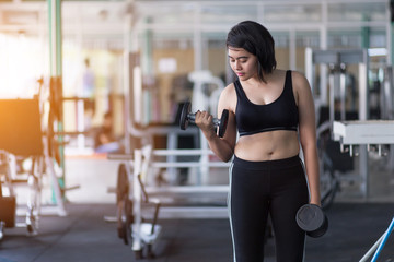 Asian woman doing workout with gym equipment and wearing sportswear to lose weight.