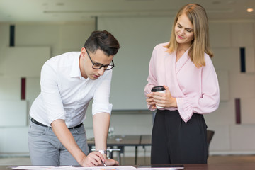 Serious male manager showing project to female executive. Young Caucasian businessman wearing glasses explaining reports to female CEO. Woman holding coffee and listening. Project presentation concept