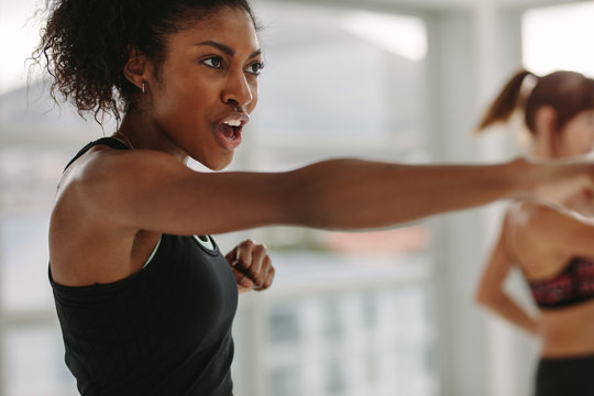 Women doing intense punching work out at the gym