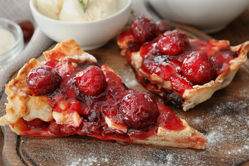Delicious pieces of cherry pie on wooden board