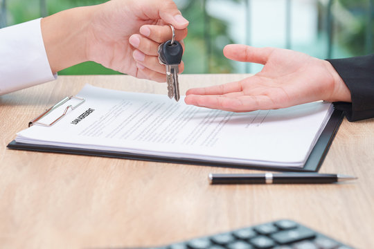 Businessman giving key over loan agreement document with calculator on wooden desk.