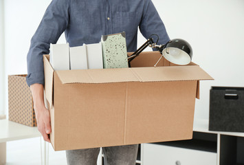 Young man holding moving box with office stuff indoors, closeup