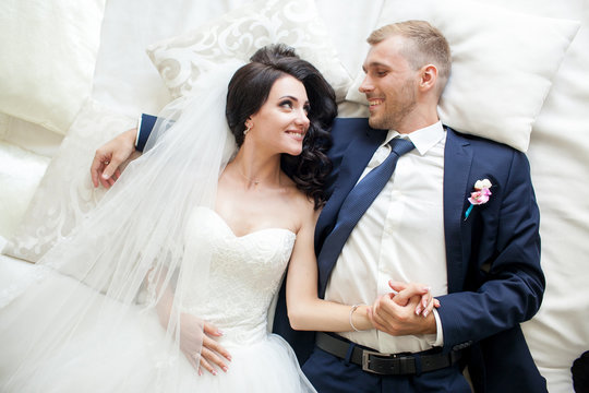 portraite happy wedding couple have fun lying on white bed in the light room. Top view