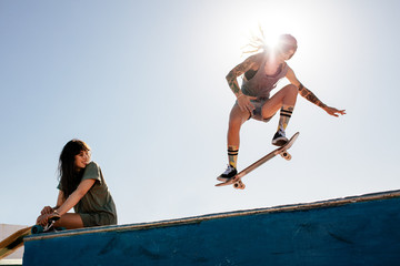 Woman skateboarding at park with friend sitting on ramp