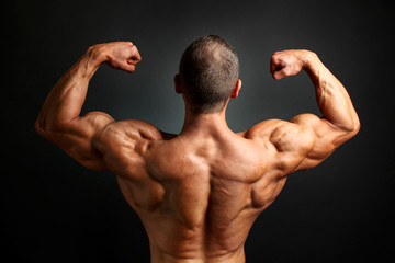 Young bodybuilder man flexing back double bicpes pose, showing his huge trapezius, rhomboid, levator and latissimus dorsi muscles. Studio shot on black background.