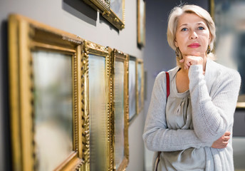 Mature woman standing in art museum near the painting in baguette