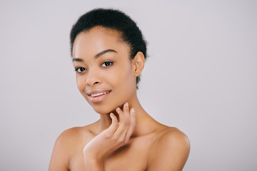 happy african american woman with perfect skin touching her face and looking at camera isolated on grey