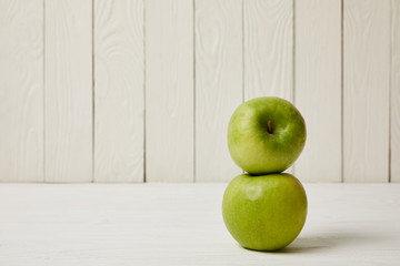 Two raw fresh green apples on wooden background with copy space