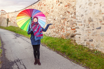 Smiling Woman with rainbow colored Umbrella at autumn, Weather concept