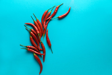 Group of little red hot chili peppers on the blue background.