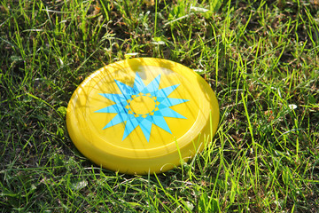 Plastic yellow frisbee flying disc lying in the grass in the park. Children's toy for active outdoor games.