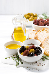 fresh organic olives, spices and bread on white background, vertical