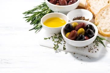 fresh organic olives, spices and bread on white wooden table