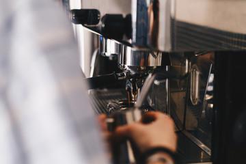 Barista prepares coffee in the coffee machine