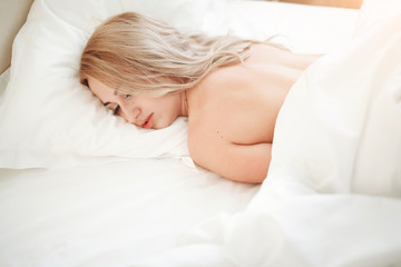 Beautiful relaxed young woman with long hair lying and sleeping on bed in bedroom