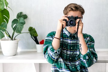 Hipster in a green shirt taking pictures on an old camera standing in the room