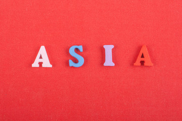 ASIA word on red background composed from colorful abc alphabet block wooden letters, copy space for ad text. Learning english concept.
