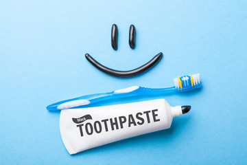 Black toothpaste from charcoal for white teeth. Toothpaste in the form of  smile on the face,  tube and  toothbrush on  blue background.