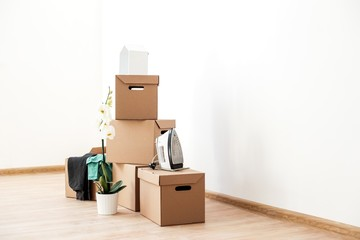 Cardboard boxes with things are on the floor in an empty room with white walls