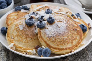homemade pancakes with blueberries and powdered sugar for breakfast, closeup