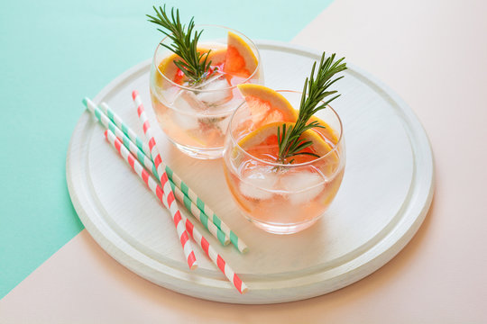 Refreshment grapefruit cocktail with rosemary on white wooden board. Healthy citrus summer drink. Mint and pink colors background