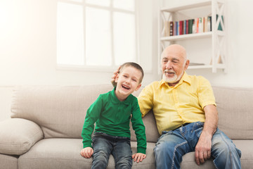 Little boy sitting on couch with his grandfather