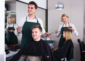 Hairdresser cutting hair of teenage