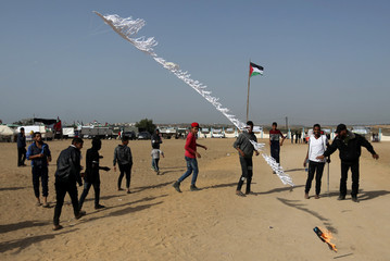 Palestinians set a kite on fire, to be thrown at the Israeli side during clashes at the Israel-Gaza border in the central Gaza strip