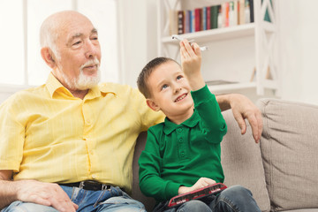 Boy playing with toy pane with his grandfather