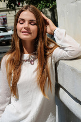 young beautiful woman with long hair dressed in white blouse staying outside дleaning against wall looking down, smiling.