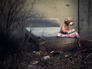 A toy bear on an old discarded bed in a dull place