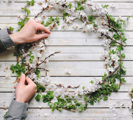 Woman hand holding beautiful white flowering apricot wreath on white table. Flat lay, top view, space for text. Romantic DIY composition