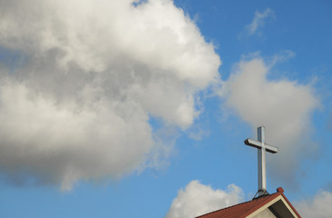 Cross on top of church, with sky and clouds behind. Good for use as background.