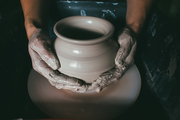 hands of a potter, creating an earthen jar on the circle. Potter at work. Top view of potter clay preparation for manufacturing making ceramic pot on the pottery wheel