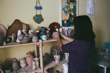 female potter holding ceramic bowl in workshop