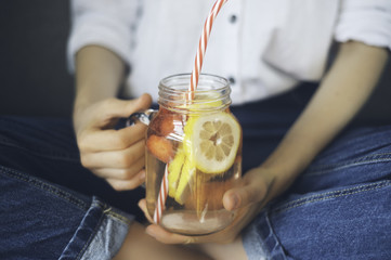 cropped shot of young woman drinking home made fresh summer drink from mason jar with straw