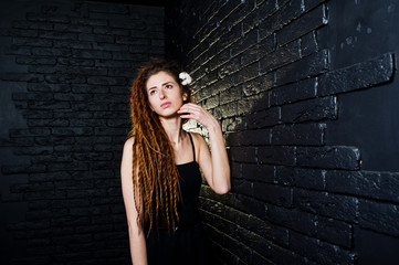 Studio shoot of girl in black with dreads on brick background.