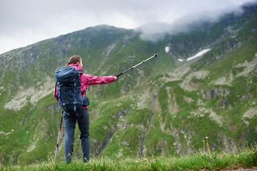 Rear view shot of a female backpacker standing on top of a hill pointing away with her trekking pole copyspace leadership achieving sports active living recreation nature environment camping.