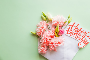 Flower composition. Creative border of pink chrysanthemums on a green background. Floral pattern. chrysanthemums with envelope . Flat lay, top view, copy space.