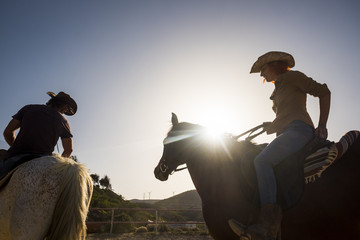 couple of cowboy ride horses with sunflare