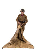 Male actor in the form of an ordinary soldier infantryman of the Russian army during the Second World War with a soldier's cloak-tent on a white background in the studio