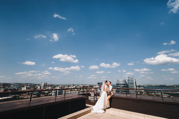 Beautiful newlyweds standing on the roof on a sunny day and hugging each other. The bride and groom in the background of a large and sunny city.