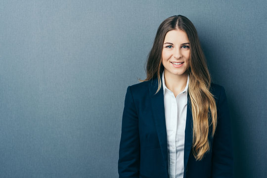Young smiling woman standing against blue wall