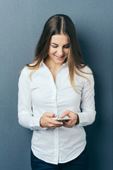 Young woman wearing white shirt using phone
