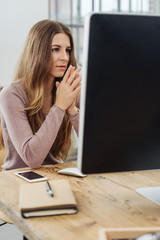 Young long-haired woman in front of computer