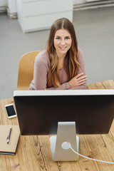 Smiling businesswoman looking over a monitor