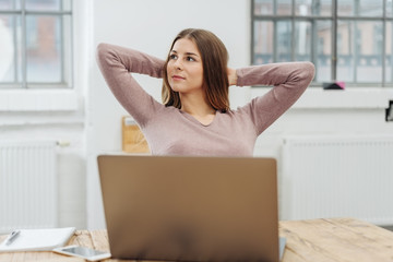 Young relaxed woman sitting in front of laptop
