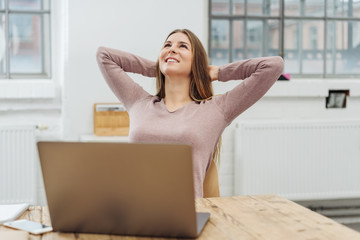 Young cheerful woman relaxing in front of laptop
